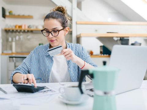 Young woman paying bills/ shopping online with credit card