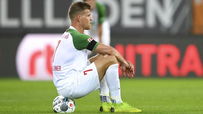 Augsburgs Florian Niederlechner sits on the ground after the German Bundesliga soccer match between FC Augsburg and SC Paderborn 07 in Augsburg, Germany, Wednesday, May 27, 2020. The German Bundesliga is the worlds first major soccer league to resume after a two-month suspension because of the coronavirus pandemic. (Matthias Hangst/Pool via AP)