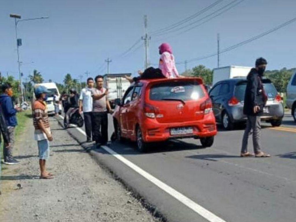Emak-emak Pemotor Ini Jatuh Terduduk di Atap Mobil, Kok Bisa Gitu?