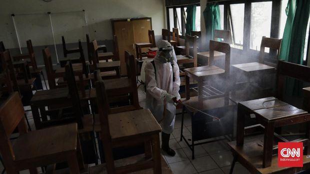 Anggota Palang Merah Indonesia menyemprotkan desinfektan dalam upaya menahan penyebaran virus corona di dalam ruang kelas di SMPN 139 dan SDN Malaka Jaya 04 Pagi. Jakarta, Selasa, 9 Juni 2020.(CNN Indonesia/ Adhi Wicaksono)