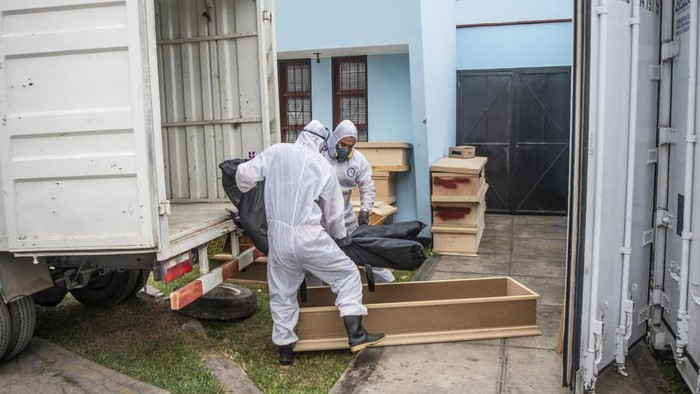 Workers carry a bag with the body of a COVID-19 victim out of a refrigerated container before its cremation at the El Angel crematorium, in Lima on May 21, 2020 - Peru has become the second Latin American country after Brazil to reach 100,000 coronavirus cases, according to health ministry figures out Wednesday. (Photo by Ernesto BENAVIDES / AFP)