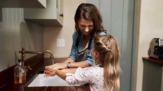 Cropped shot of a woman and her young daughter washing their hands in the kitchen at home