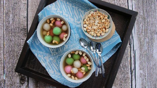 A Chinese Peranakan dessert of glutinous rice balls in warm ginger soup. Served in vintage ceramic bowls with extra peanuts, also in vintage saucer. This dessert dish is arranged on a wooden tray that has been lined with a batik napkin. The tray is then placed on a rustic wooden table.
