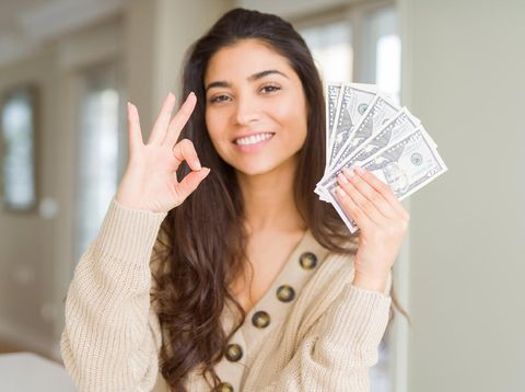 Young woman holding 50 dollars bank notes doing ok sign with fingers, excellent symbol