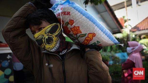 Warga membopong karung beras isi paket bansos di Kelurahan Pondok Kelapa, Jakarta, Jumat, 12 Juni 2020. Bansos program keluarga harapan (PKH) sudah berlangsung sejak April untuk melindungi keluarga prasejahtera dari dampak Covid-19. Isi bansos yang diterima warga berupa beras, telur, jeruk dan ayam potong. CNNIndonesia/Safir Makki