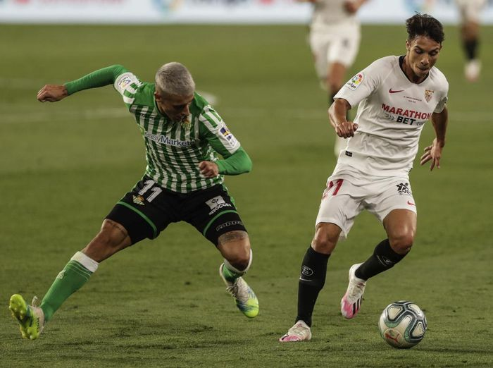 Betis Cristian Tello, left, and Sevillas Oliver Torres duel for the ball during their Spanish La Liga soccer match in Seville, Spain, Thursday, June 11, 2020. With virtual crowds, daily matches and lots of testing for the coronavirus, soccer is coming back to Spain. The Spanish league resumes this week more than three months after it was suspended because of the pandemic, becoming the second top league to restart in Europe. The Bundesliga was first. The Premier League and the Italian league should be next in the coming weeks. (AP Photo)