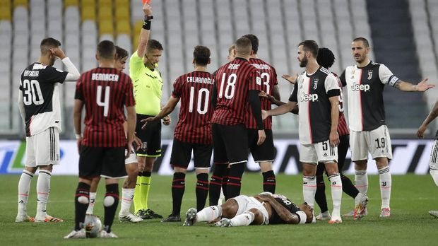 AC Milan's Ante Rebic, center, gets a red card during an Italian Cup second leg soccer match between Juventus and AC Milan at the Allianz stadium, in Turin, Italy, Friday, June 12, 2020. The match was being played without spectators because of the coronavirus lockdown. (AP Photo/Luca Bruno)