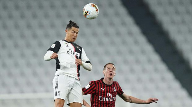 Juventus' Cristiano Ronaldo heads the ball past AC Milan's Andrea Conti during an Italian Cup second leg soccer match between Juventus and AC Milan at the Allianz stadium, in Turin, Italy, Friday, June 12, 2020. The match was being played without spectators because of the coronavirus lockdown. (Spada/LaPresse via AP)