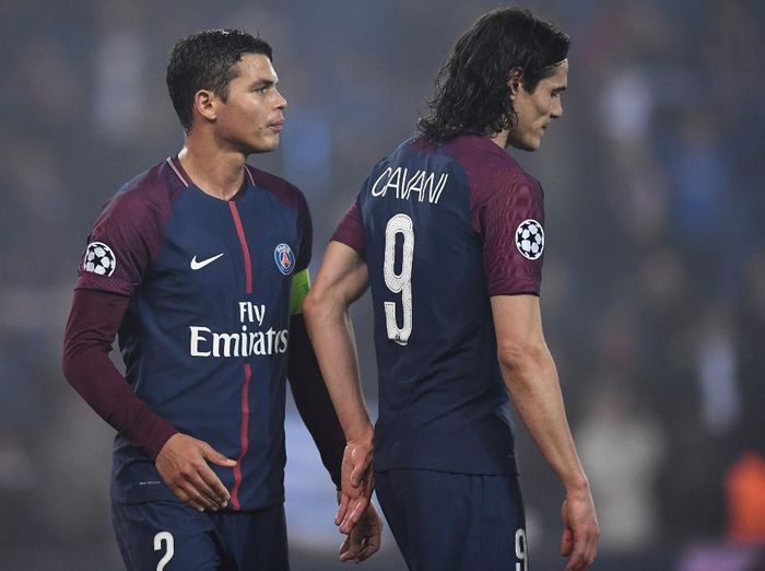 (FILES) In this file photo taken on March 6, 2018 Paris Saint-Germains Uruguayan forward Edinson Cavani (R) and Paris Saint-Germains Brazilian defender Thiago Silva react after losing the UEFA Champions League round of 16 second leg football match between Paris Saint-Germain (PSG) and Real Madrid, at the Parc des Princes stadium in Paris. - While waiting for the restart of the UEFA Champions League in August 2020, the Paris Saint-Germain (PSG) football club is already working and thinking about next season.   With losses estimated by the club at more than 200 M EUR after the end of Ligue 1, due to the COVID-19 pandemic, the question of saving a transfer to find a replacement of the caliber of Edinson Cavani (33 years) or of Thiago Silva (35 years), respectively top scorer in history and captain of the Paris club, is very important. (Photo by FRANCK FIFE / AFP)