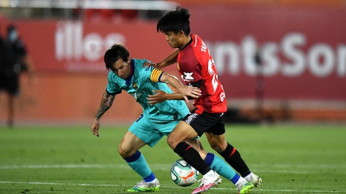 MALLORCA, SPAIN - JUNE 13: Lionel Messi of FC Barcelona battles for possession with Takefusa Kubo of RCD Mallorca during the La Liga match between RCD Mallorca and FC Barcelona at Estadio de Son Moix on June 13, 2020 in Mallorca, Spain. (Photo by David Ramos/Getty Images)