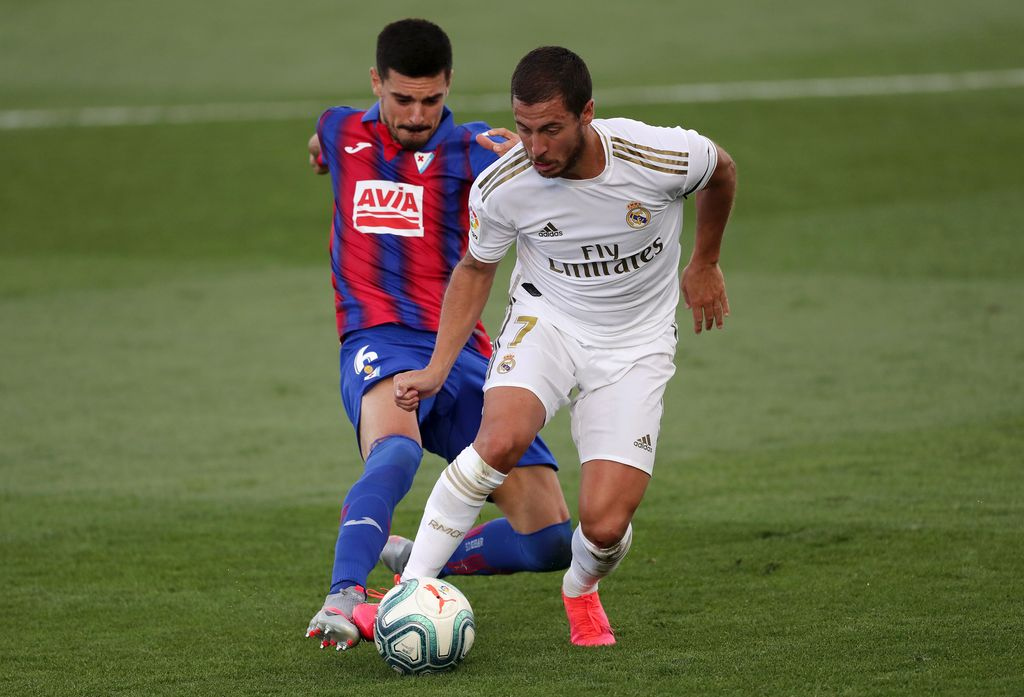MADRID, SPAIN - JUNE 14: Segio Alvarez of Eibar battles for possession with Eden Hazard of Real Madrid  during the Liga match between Real Madrid CF and SD Eibar SAD at Estadio Alfredo Di Stefano on June 14, 2020 in Madrid, Spain. (Photo by Gonzalo Arroyo Moreno/Getty Images)