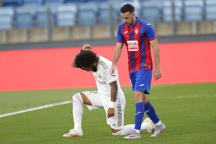 Real Madrids Marcelo takes a knee as he celebrates his goal during the Spanish La Liga soccer match between Real Madrid and Eibar at Alfredo di Stefano stadium in Madrid, Spain, Sunday, June 14, 2020. (AP Photo/Bernat Armangue)