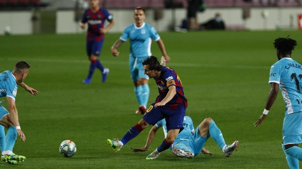 FC Barcelona's Lionel Messi, center, vies for the ball with Leganes' Ruben Perez, second right, during the Spanish La Liga soccer match between FC Barcelona and Leganes at the Camp Nou stadium in Barcelona, Spain, Tuesday, June 16, 2020. (AP Photo/Joan Montfort)