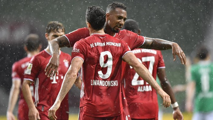 Bayerns Robert Lewandowski, foreground, celebrates with his teammate Bayerns Jerome Boateng after scoring his sides opening goal during the German Bundesliga soccer match between Werder Bremen and Bayern Munich in Bremen, Germany, Tuesday, June 16, 2020. Because of the coronavirus outbreak all soccer matches of the German Bundesliga take place without spectators. (AP Photo/Martin Meissner, Pool)