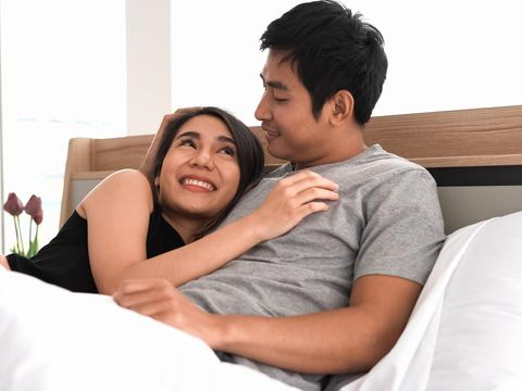 Young loving couple in bed. Happy couple relaxing in bed.