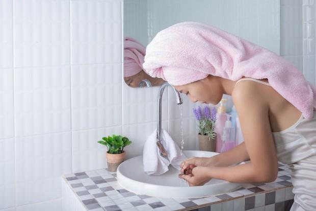 Membilas wajah dengan air setelah menggunakan cleansing oil