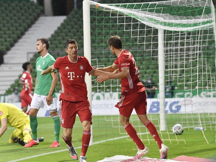 Bayerns Robert Lewandowski, second right, celebrates with Bayerns Thomas Mueller after scoring a goal later disallowed for offside during the German Bundesliga soccer match between Werder Bremen and Bayern Munich in Bremen, Germany, Tuesday, June 16, 2020. Because of the coronavirus outbreak all soccer matches of the German Bundesliga take place without spectators. (AP Photo/Martin Meissner, Pool)