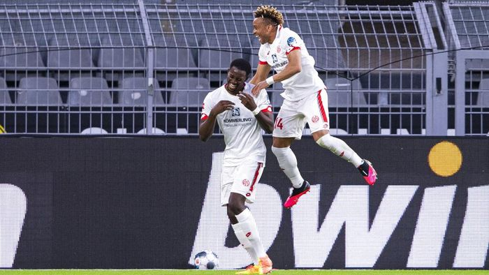 Mainzs scorer Jean-Philippe Mateta, left, and his teammate Pierre Kunde Malong, right, celebrate their sides second goal during the German Bundesliga soccer match between Borussia Dortmund and 1. FSV Mainz 05 in Dortmund, Germany, Wednesday, June 17, 2020. (Guido Kirchner/DPA via AP, Pool)