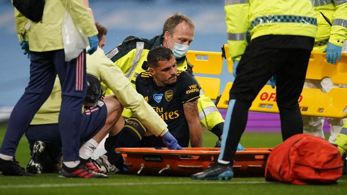 MANCHESTER, ENGLAND - JUNE 17: Granit Xhaka of Arsenal reacts as he receives medical treatment before being helped onto a stretcher during the Premier League match between Manchester City and Arsenal FC at Etihad Stadium on June 17, 2020 in Manchester, United Kingdom. (Photo by Dave Thompson/ Pool via Getty Images)