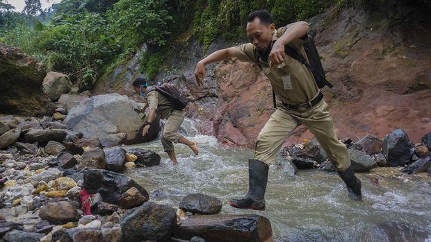 Kepala Sekolah SMP N 4 Bawang Mulud Sugito (kanan) dan guru Wiyata Bhakti melewati aliran sungai di dasar bukit saat mengantar lembar tugas siswa secara langsung ke rumahnya di Pranten, Kecamatan Bawang, Kabupaten Batang, Jawa Tengah.