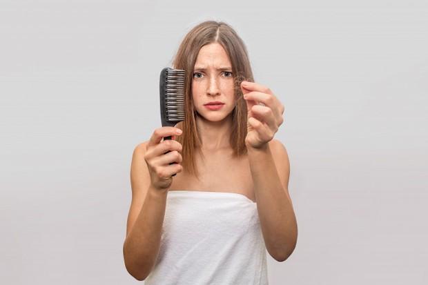 Seorang wanita memegang sisir dan rambutnya yang rontok.