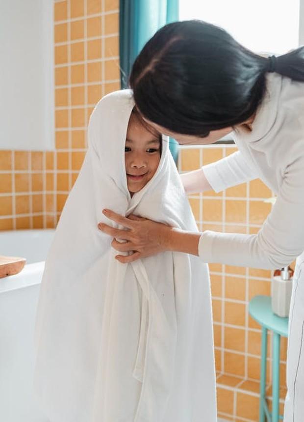 Seorang anak saat sedang menggunakaan handuk setelah mandi dan membersihkan wajah.