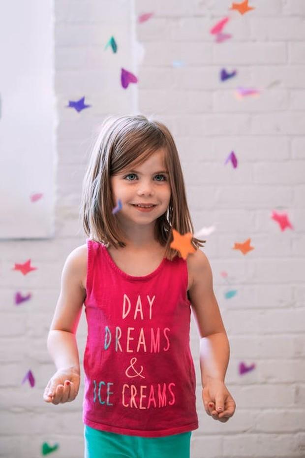 Seorang anak perempuan menggunakan baju pink.