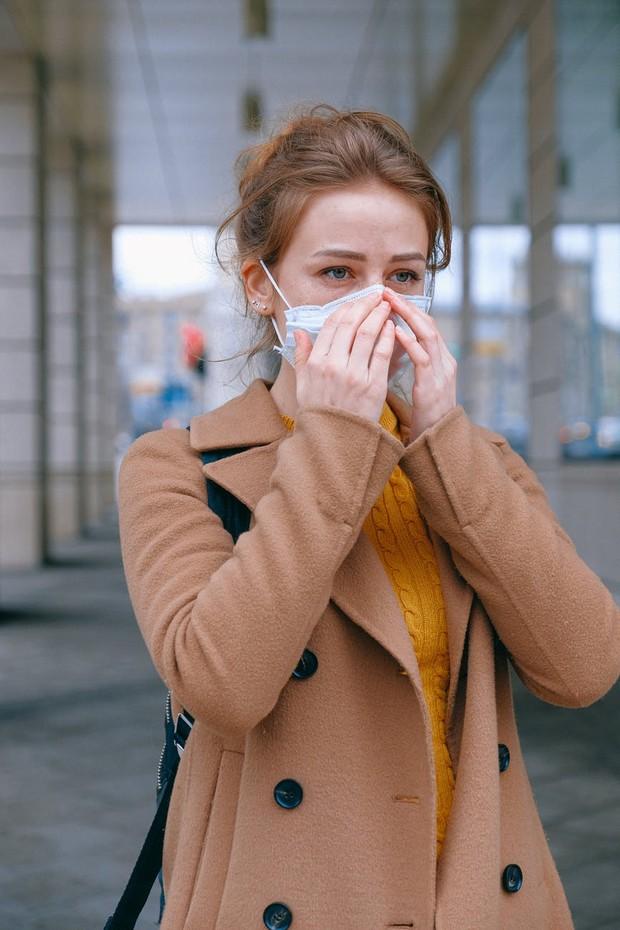 Seorang wanita merapikan masker yang sedang digunakan untuk melindungi diri dari risiko penularan virus.
