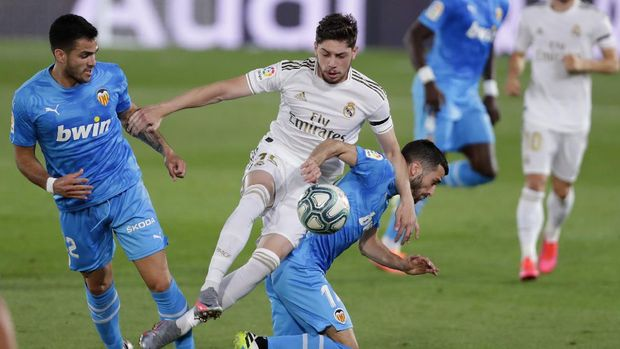 Real Madrid's Federico Valverde, center, challenges for the ball with Valencia's Jose Luis Gaya, right, and Valencia's Maxi Gomez during the Spanish La Liga soccer match between Real Madrid and Valencia at Alfredo di Stefano stadium in Madrid, Spain, Thursday, June 18, 2020. (AP Photo/Manu Fernandez)