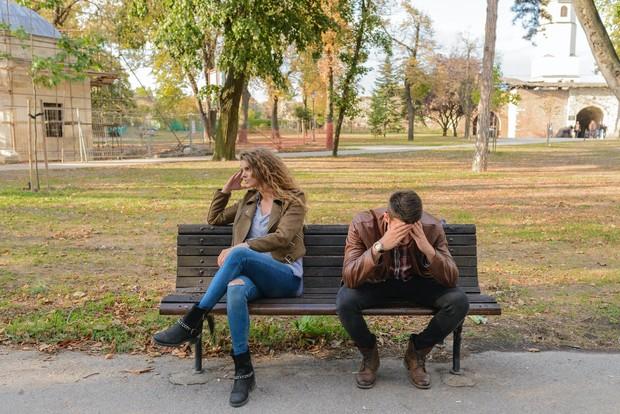 pasangan duduk di taman sedang bertengkar