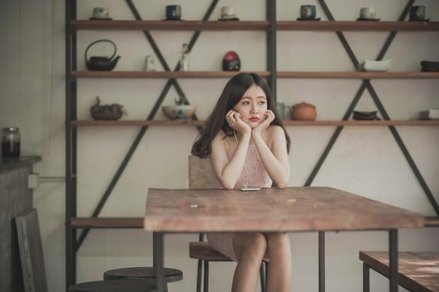 wanita yang sedang duduk dan termenung sendirian