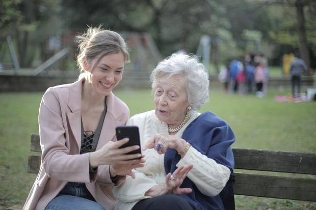 orang tua dan anak sedang bermain ponsel