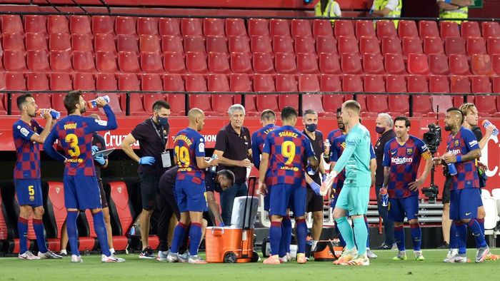 Barcelonas Spanish coach Quique Setien (C) speaks to players during the Spanish league football match between Sevilla FC and FC Barcelona at the Ramon Sanchez Pizjuan stadium in Seville on June 19, 2020. (Photo by CRISTINA QUICLER / AFP)