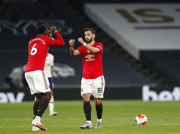 Manchester Uniteds Bruno Fernandes, right, celebrates with Paul Pogba after scoring his sides first goal during the English Premier League soccer match between Tottenham Hotspur and Manchester United at Tottenham Hotspur Stadium in London, England, Friday, June 19, 2020. (AP Photo/Matt Childs, Pool)