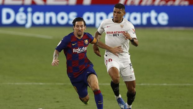 Barcelona's Lionel Messi, left, vies for the ball against Sevilla's Diego Carlos during the Spanish La Liga soccer match between Sevilla and FC Barcelona at the Ramon Sanchez-Pizjuan stadium in Seville, Spain, Friday, June 19, 2020. (AP Photo/Angel Fernandez)