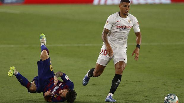 Barcelona's Lionel Messi, left, falls next to Sevilla's Diego Carlos during the Spanish La Liga soccer match between Sevilla and FC Barcelona at the Ramon Sanchez-Pizjuan stadium in Seville, Spain, Friday, June 19, 2020. (AP Photo/Angel Fernandez)