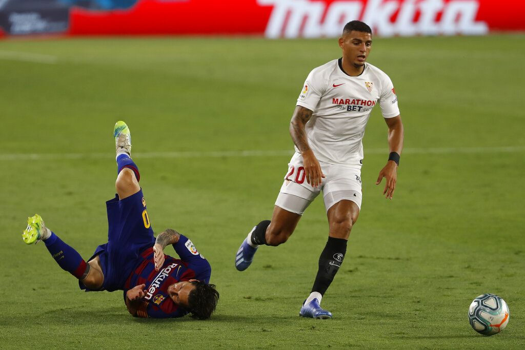 Barcelona's Lionel Messi, left, falls next to Sevilla's Diego Carlos during the Spanish La Liga soccer match between Sevilla and FC Barcelona at the Ramon Sanchez-Pizjuan stadium in Seville, Spain, Friday, June 19, 2020. (AP Photo/Angel Fernandez)