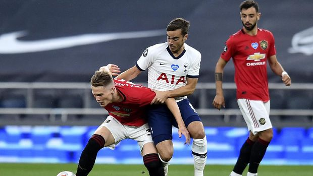 Manchester United's Axel Tuanzebe, left, and Tottenham's Harry Winks battle for the ball during the English Premier League soccer match between Tottenham Hotspur and Manchester United at Tottenham Hotspur Stadium in London, England, Friday, June 19, 2020. (AP Photo/Glyn Kirk, Pool)