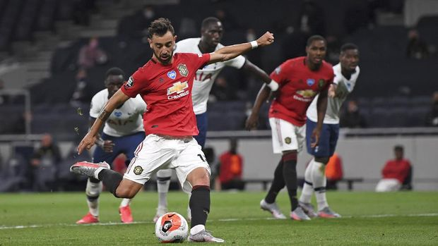 Manchester United's Bruno Fernandes scores from the spot for his side's first goal during the English Premier League soccer match between Tottenham Hotspur and Manchester United at Tottenham Hotspur Stadium in London, England, Friday, June 19, 2020. (AP Photo/Shaun Botterill, Pool)