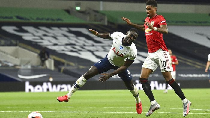 Tottenhams Davinson Sanchez, left, reacts as he battles with and Manchester Uniteds Marcus Rashford for the ball during the English Premier League soccer match between Tottenham Hotspur and Manchester United at Tottenham Hotspur Stadium in London, England, Friday, June 19, 2020. (AP Photo/Glyn Kirk, Pool)