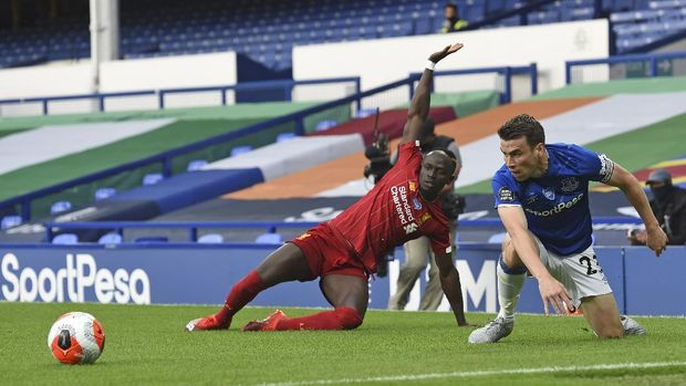 Everton's Seamus Coleman, right, battles for the ball with Liverpool's Sadio Mane during the English Premier League soccer match between Everton and Liverpool at Goodison Park in Liverpool, England, Sunday, June 21, 2020. (Peter Powell/Pool via AP)