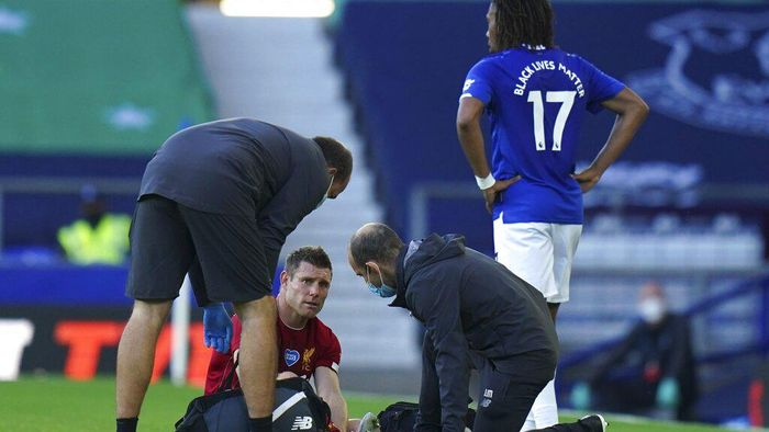 Liverpools James Milner gets injured during the English Premier League soccer match between Everton and Liverpool at Goodison Park in Liverpool, England, Sunday, June 21, 2020. (AP photo/Jon Super, Pool)