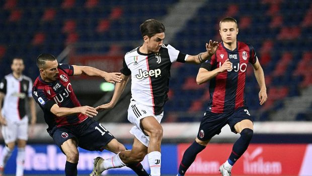 Juventus' Paulo Dybala, center, in action with Bologna's Nicola Sansone, left, during the Serie A soccer match between Bologna FC and Juventus FC at Stadio Renato Dall'Ara stadium in Bologna, Monday June 22, 2020. (Massimo Paolone/LaPresse via AP)