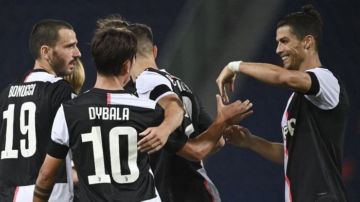 Juventus Paulo Dybala, no. 10, celebrates scoring with teammate Cristiano Ronaldo, right, and teammates during the Serie A soccer match between Bologna FC and Juventus FC at Stadio Renato DallAra stadium in Bologna, Monday June 22, 2020. (Massimo Paolone/LaPresse via AP)