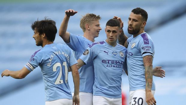Manchester City's Phil Foden, second right, is congratulated by teammates after scoring his teams first goal during the English Premier League soccer match between Manchester City and Burnley at Etihad Stadium, in Manchester, England, Monday, June 22, 2020. (AP Photo/Martin Rickett,Pool)