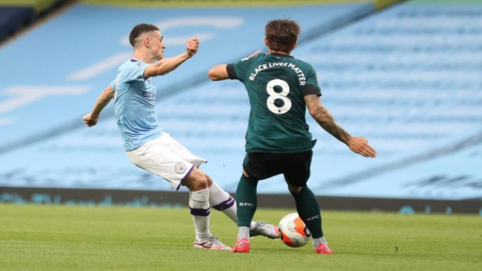 MANCHESTER, ENGLAND - JUNE 22: Phil Foden of Manchester City scores his teams first goal during the Premier League match between Manchester City and Burnley FC at Etihad Stadium on June 22, 2020 in Manchester, England. Football stadiums around Europe remain empty due to the Coronavirus Pandemic as Government social distancing laws prohibit fans inside venues resulting in all fixtures being played behind closed doors. (Photo by Martin Rickett/Pool via Getty Images)