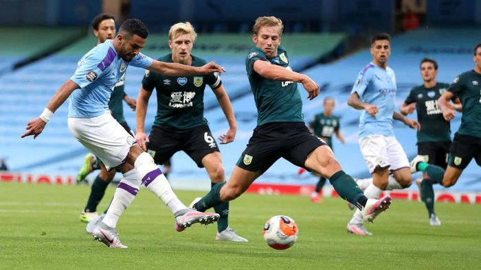 MANCHESTER, ENGLAND - JUNE 22: Riyad Mahrez of Manchester City scores his teams second goal during the Premier League match between Manchester City and Burnley FC at Etihad Stadium on June 22, 2020 in Manchester, England. Football stadiums around Europe remain empty due to the Coronavirus Pandemic as Government social distancing laws prohibit fans inside venues resulting in all fixtures being played behind closed doors. (Photo by Martin Rickett/Pool via Getty Images)