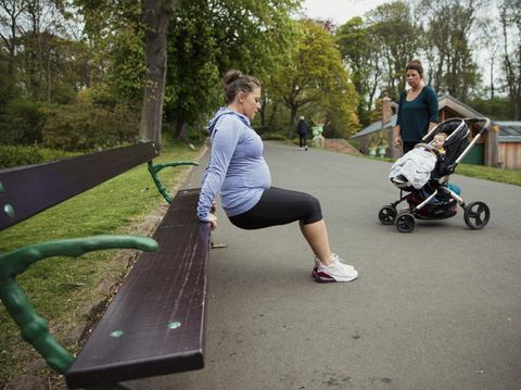 A pregnant fitness instructor is demonstrating how to do a reverse push up to one of the mothers in her fitness bootcamp.