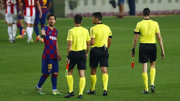 Barcelona's Lionel Messi, left, talks with the referee Jesus Gil Manzano during the Spanish La Liga soccer match between FC Barcelona and Athletic Bilbao at the Camp Nou stadium in Barcelona, Spain, Tuesday, June 23, 2020. (AP Photo/Joan Monfort)