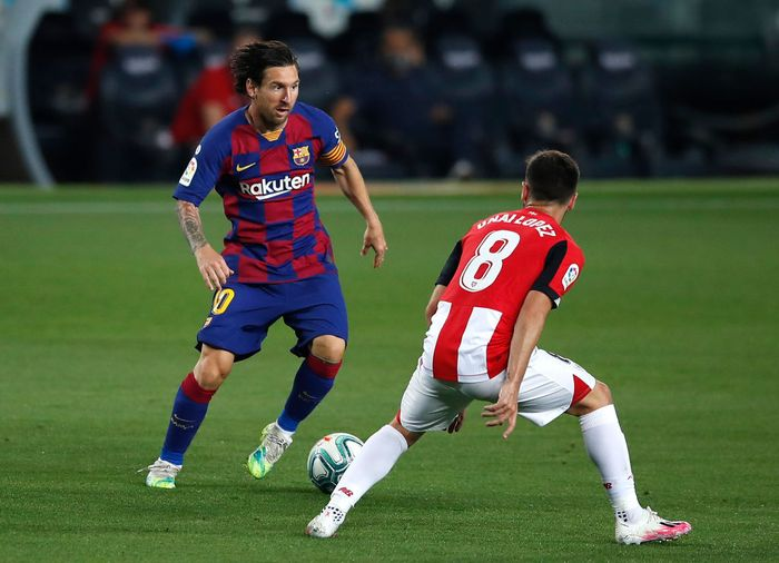 BARCELONA, SPAIN - JUNE 23: Lionel Messi of Barcelona takes on Unai Lopez of Athletic Bilbao during the Liga match between FC Barcelona and Athletic Club at Camp Nou on June 23, 2020 in Barcelona, Spain. Football Stadiums around Europe remain empty due to the Coronavirus Pandemic as Government social distancing laws prohibit fans inside venues resulting in all fixtures being played behind closed doors. (Photo by Eric Alonso/Getty Images)